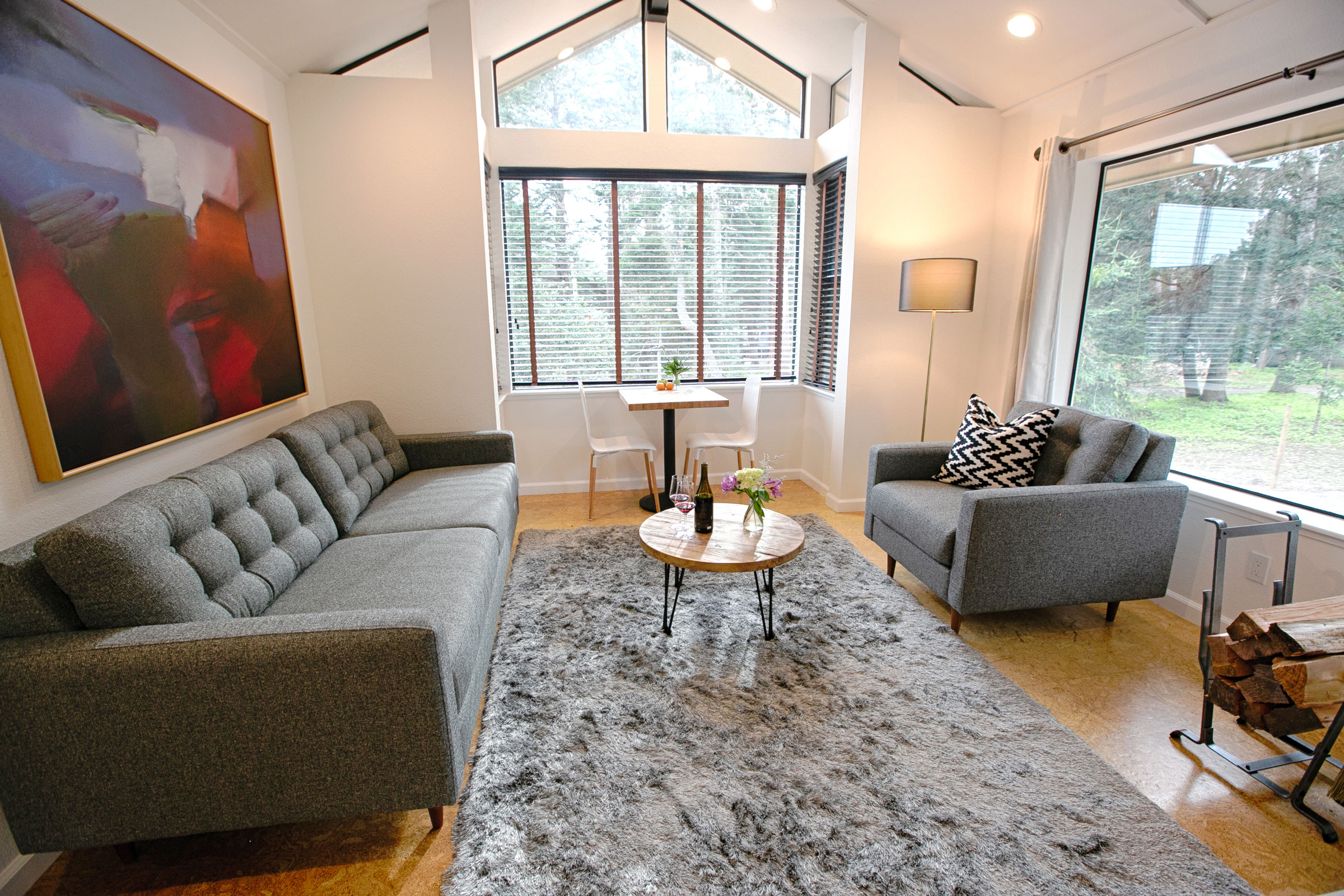 The sitting area of room 202 in the Lodge at Glendeven of Mendocino with plush grey rug, nook with table and chairs, and contemporary art.