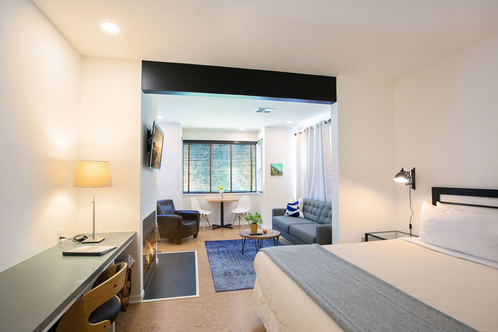 Room 103 in the Lodge with a comfy bed, wood-burning fireplace, sitting area, desk space, and cork floors