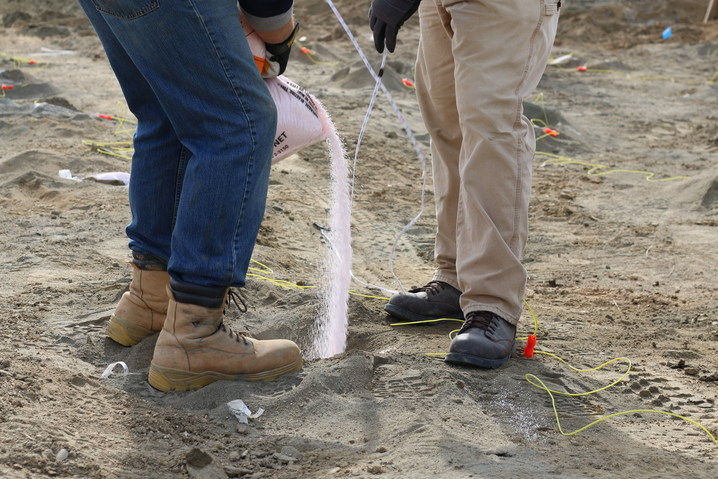 workers pouring explosive material into drilled holes at a project site