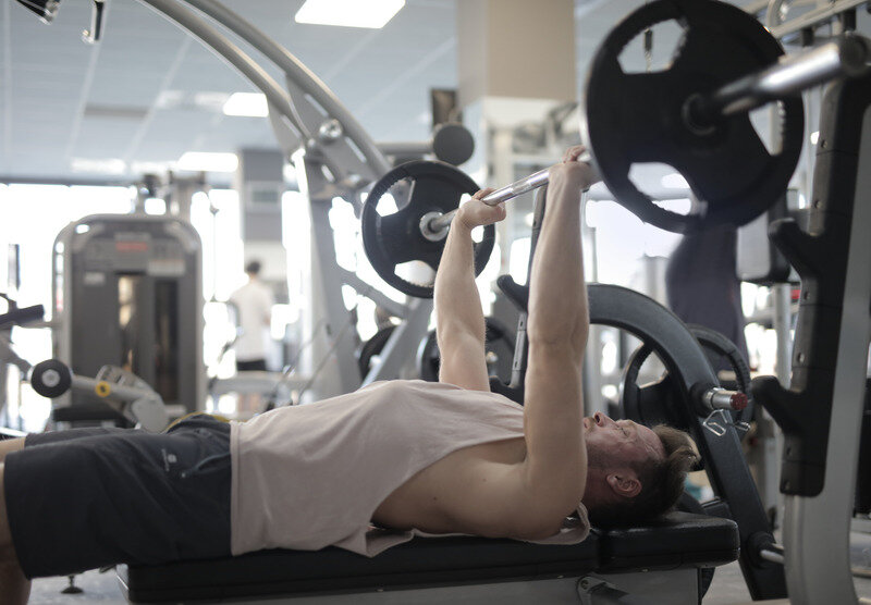 Canva - Muscular sportsman training with heavy barbell during weightlifting workout in modern gym.jpg
