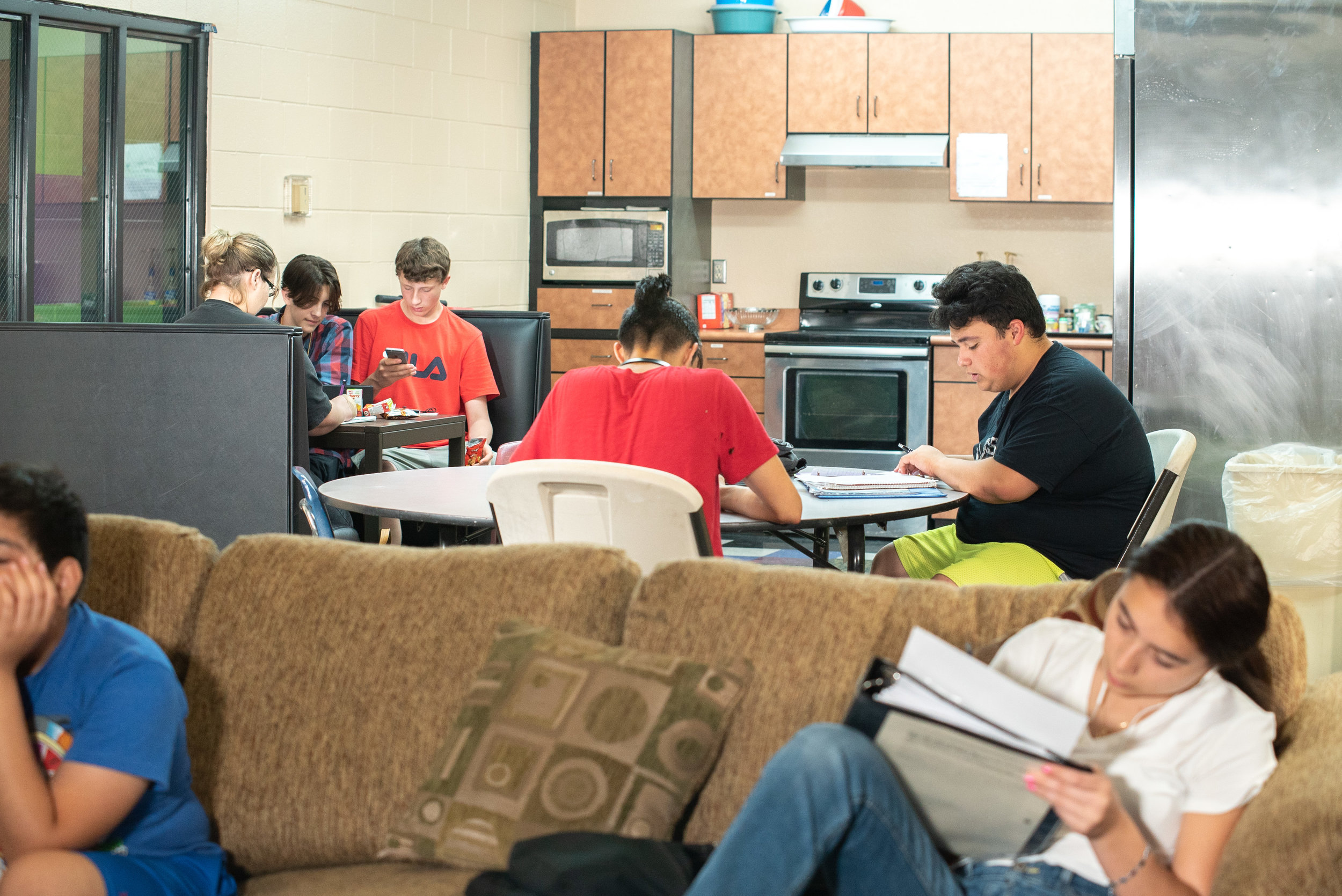 Teens enjoy a snack with friends while finishing homework in the kitchen area.
