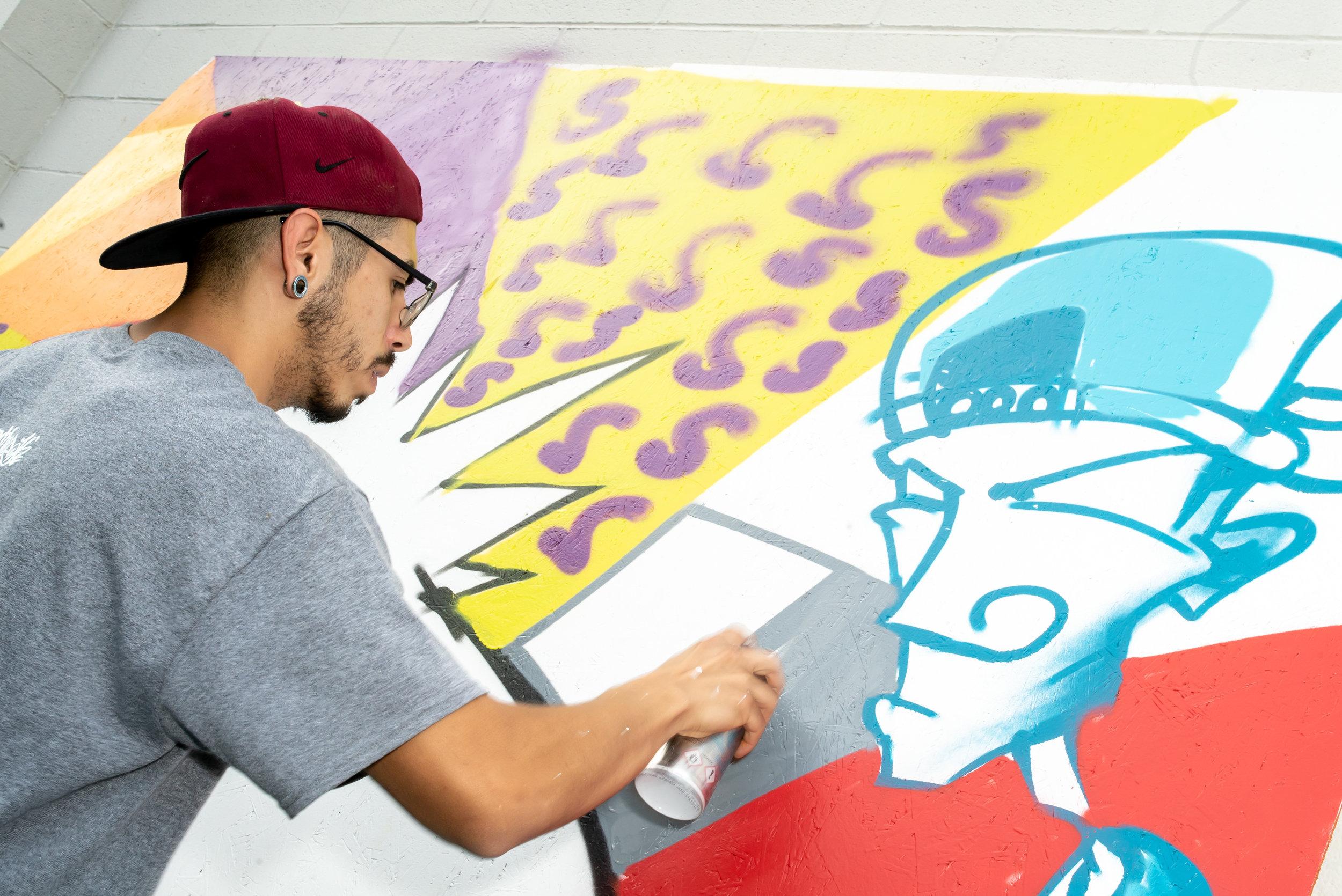 Volunteer graffiti artist, Reggie, creating a live piece.