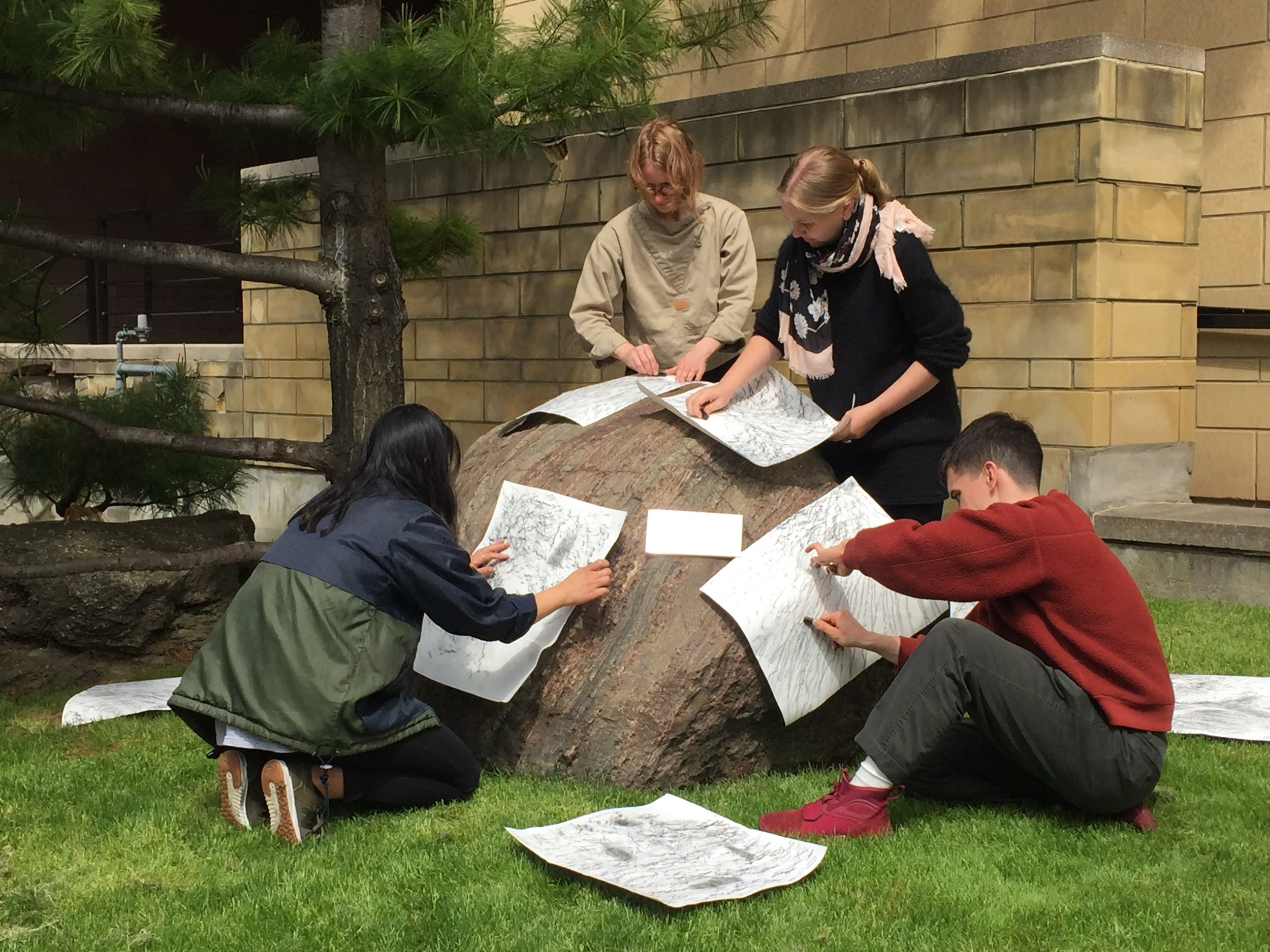 Workshop participants make rubbings of erratic glaciers as part of the boulder kite making (photo by Meghan Price)