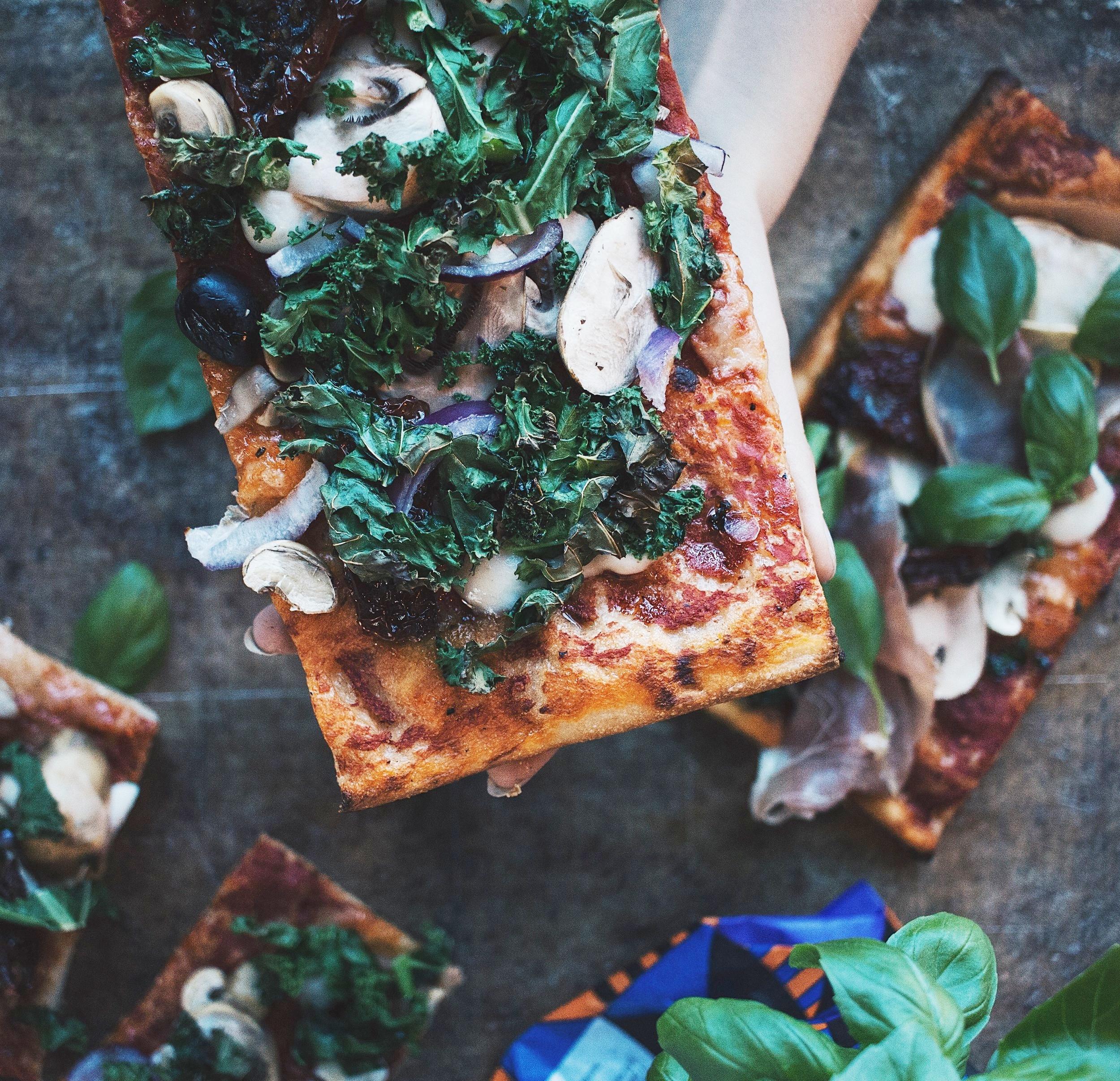 Pizza-på vår egen surdeg, toppad med säsongens råvaror. -