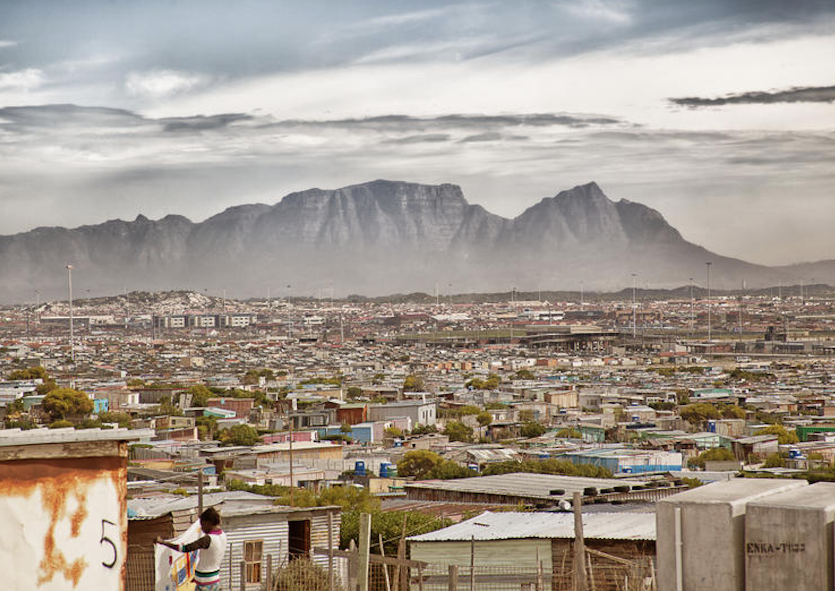"Khayelitsha means ""our new home"" in Xhosa, one of the official languages of the country. It is the second largest township in South Africa after Soweto. Table Mountain in the background."