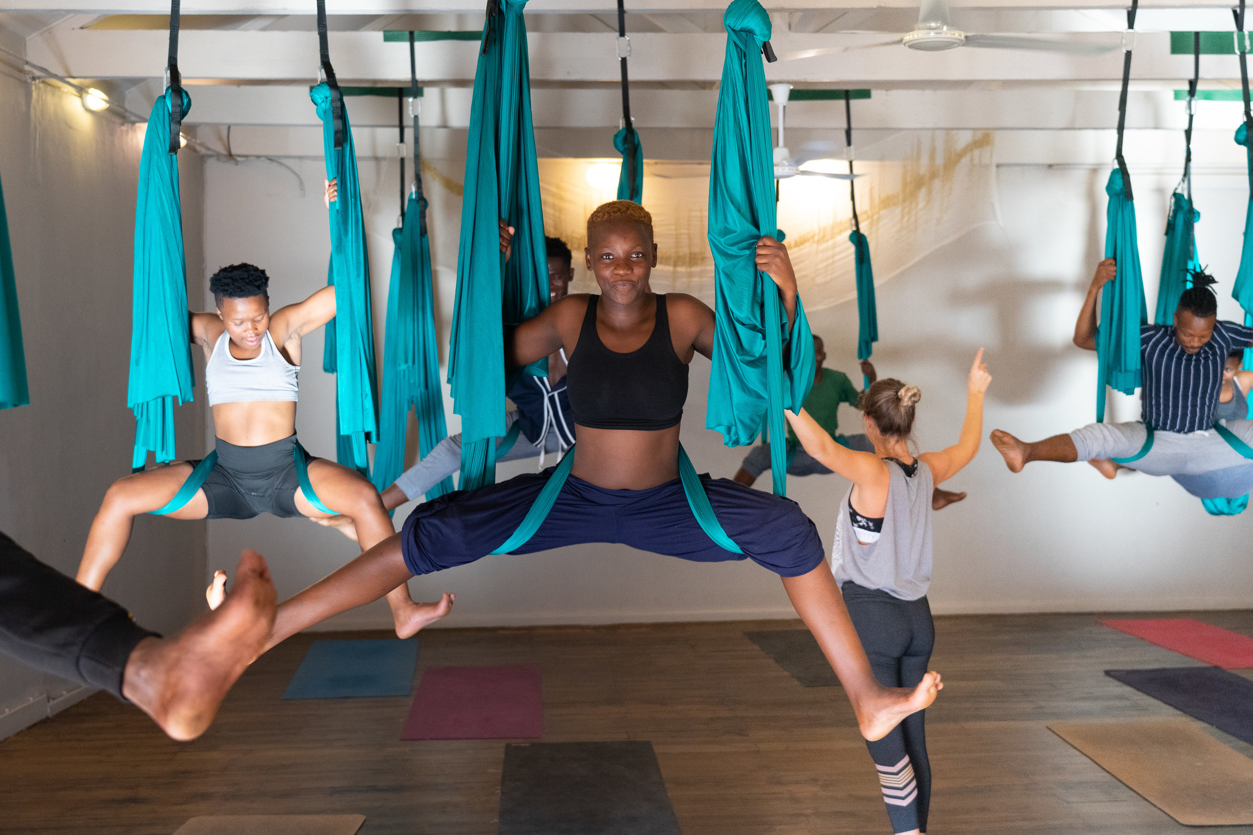 "Sinazo, Yolanda, Mthetheleli, and their peers rising above the floor of The Shala Yoga School in ""diaper wrap straddle pose"" guided by the talented Kathleen Booyse."