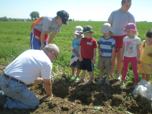 Farmer John showing kids how to plant in the ground