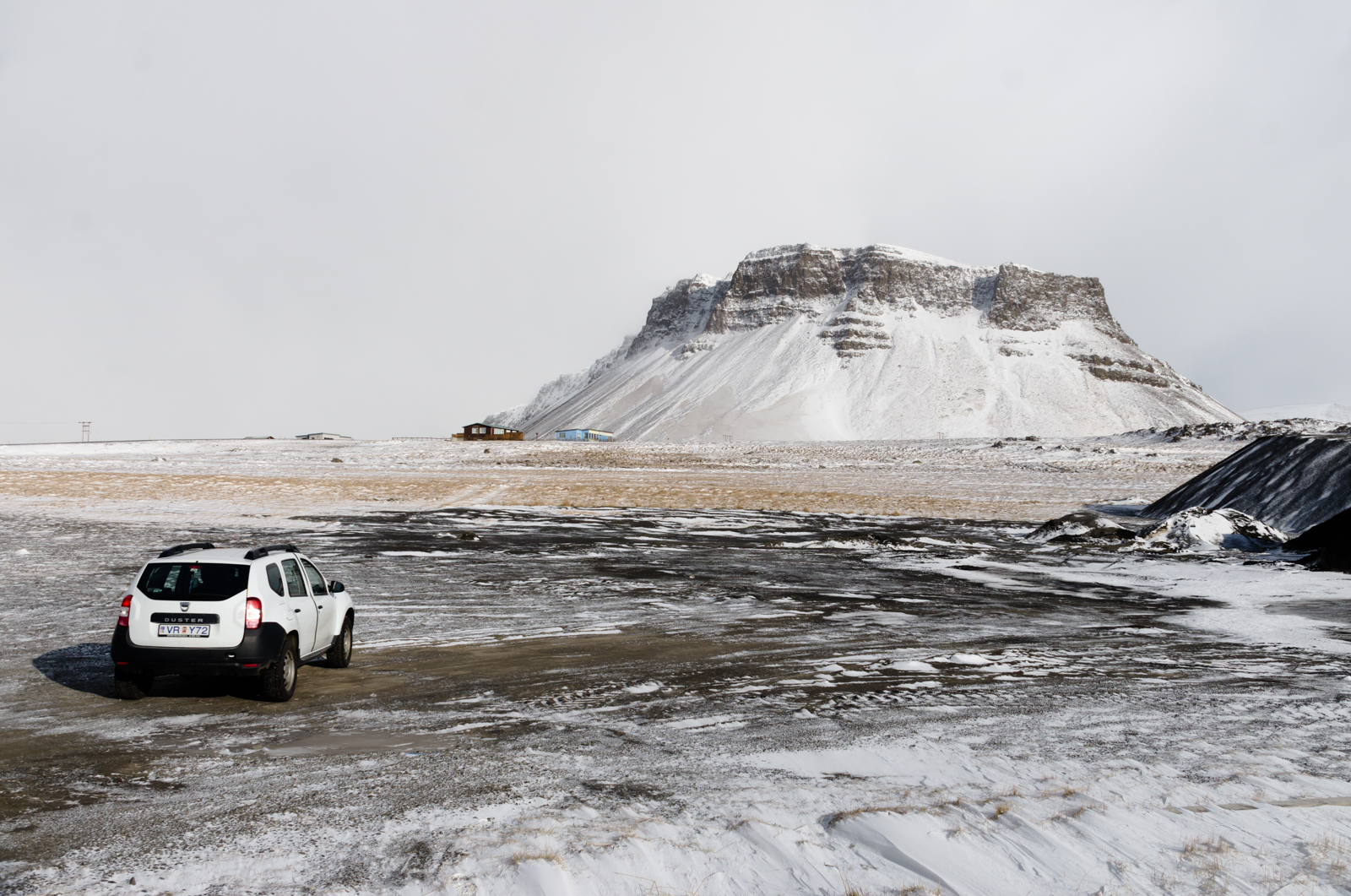 A 4x4 car parked in a vast field in front of a snow covered mountain in Iceland