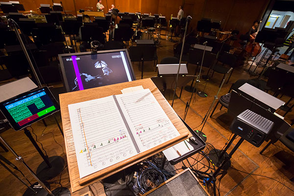 """Technology is essential not only for the creation of film-with-live-orchestra programs with classics like  On the Waterfront , but also for performing them. In addition to the musical score, the conductor keeps an eye on a visual """"click-track"""" to ensure that the orchestra remains in time with the film as it plays. Digital playback technology has made rehearsals more manageable as well, allowing for faster and more precise selection of scenes."""