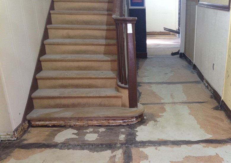 All floors are being replaced - here we see the front stairs and hallway after the old flooring has been removed.