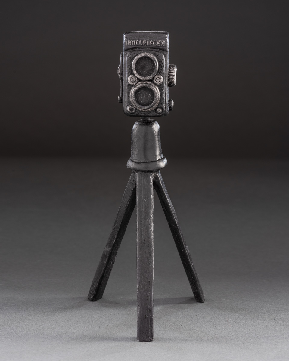 """Henry's Camera - """"Not every artistic person should have to be a photographer, but every photographer should beartistic.""""- Pradeepa Pandiyan.The inspiration for this vintage Rolleiflex camera and tripod comes from our sculpture """"Henry"""". Named for famed fashion photographer Henry Clark.Cast marble. Measures 8""""ht × 3.5""""wd.SEE PRICING"""