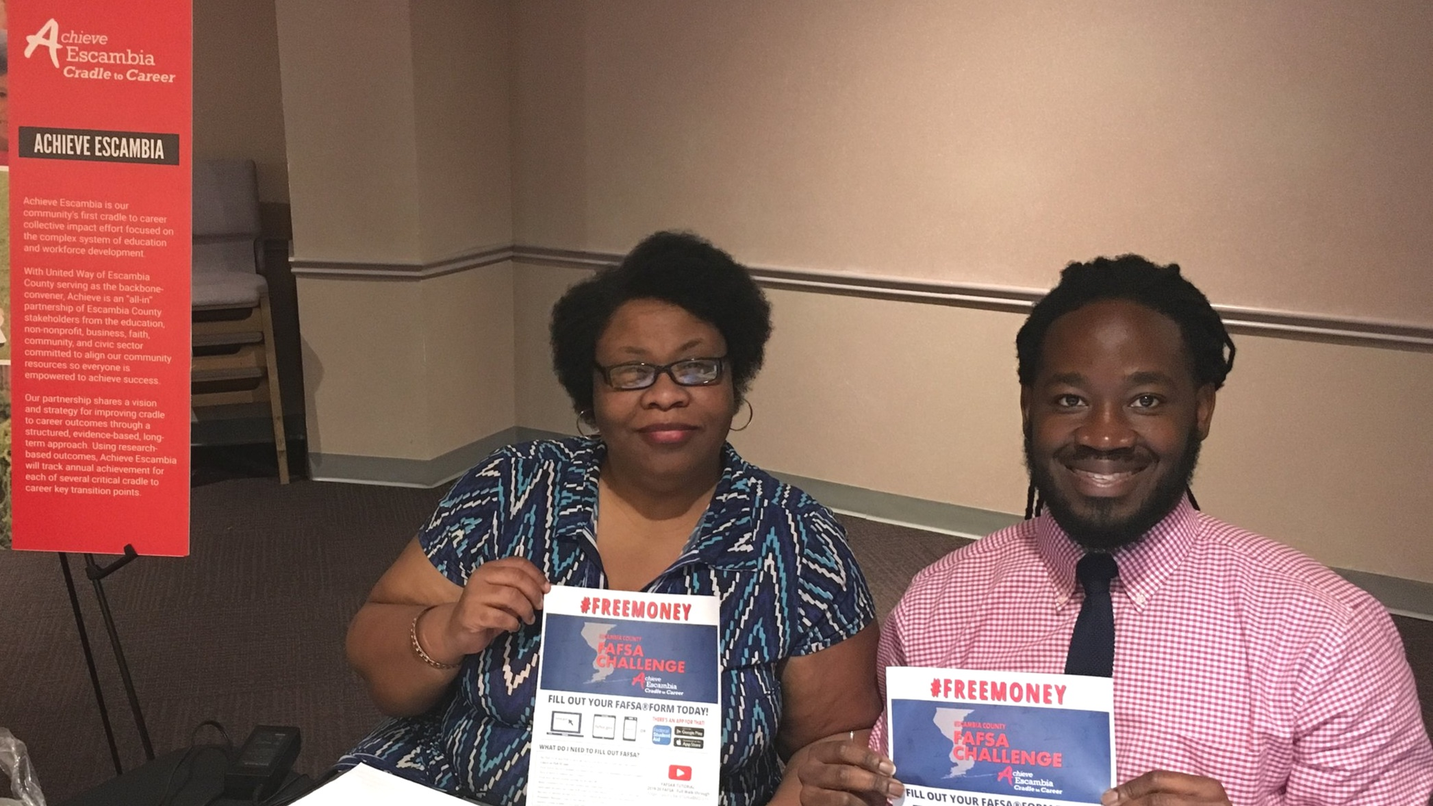 Valery Hollinger, left, works with continuous improvement intern Max Petion at the Escambia County FAFSA Challenge table during the Escambia County School District's Career University day.