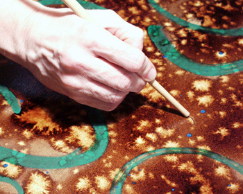 9. Taking the end of a small paintbrush, you can write, draw, scratch, etc. marks into the still wet walnut ink. This will create marks darker than the background which adds a nice texture to the paper.