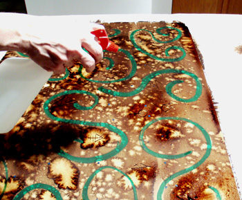 13. To create even more movement of the ink after the symbols were drawn in, Debbie applied more water with a spray bottle. It was applied only to certain areas of the paper where more pattern/movement was desired.