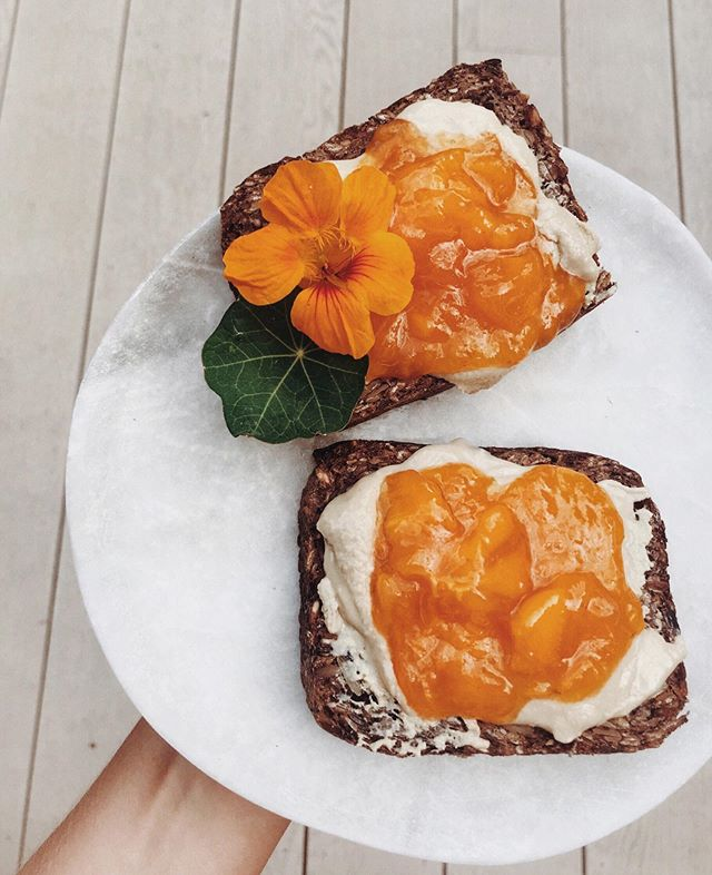 one of my summertime rotations. persimmon + tahini on toasted sourdough rye with a nasturtium flower 🔶✨