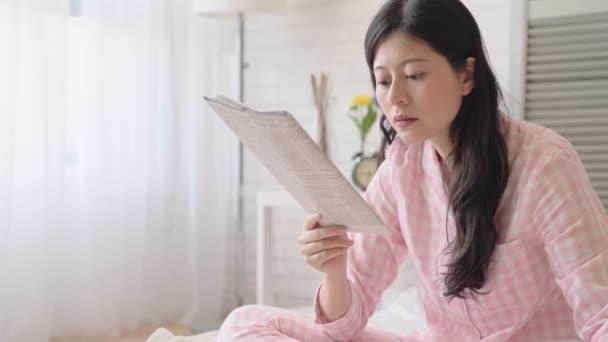 depositphotos_195279664-stock-video-asian-lady-reading-newspaper-drinking.jpg