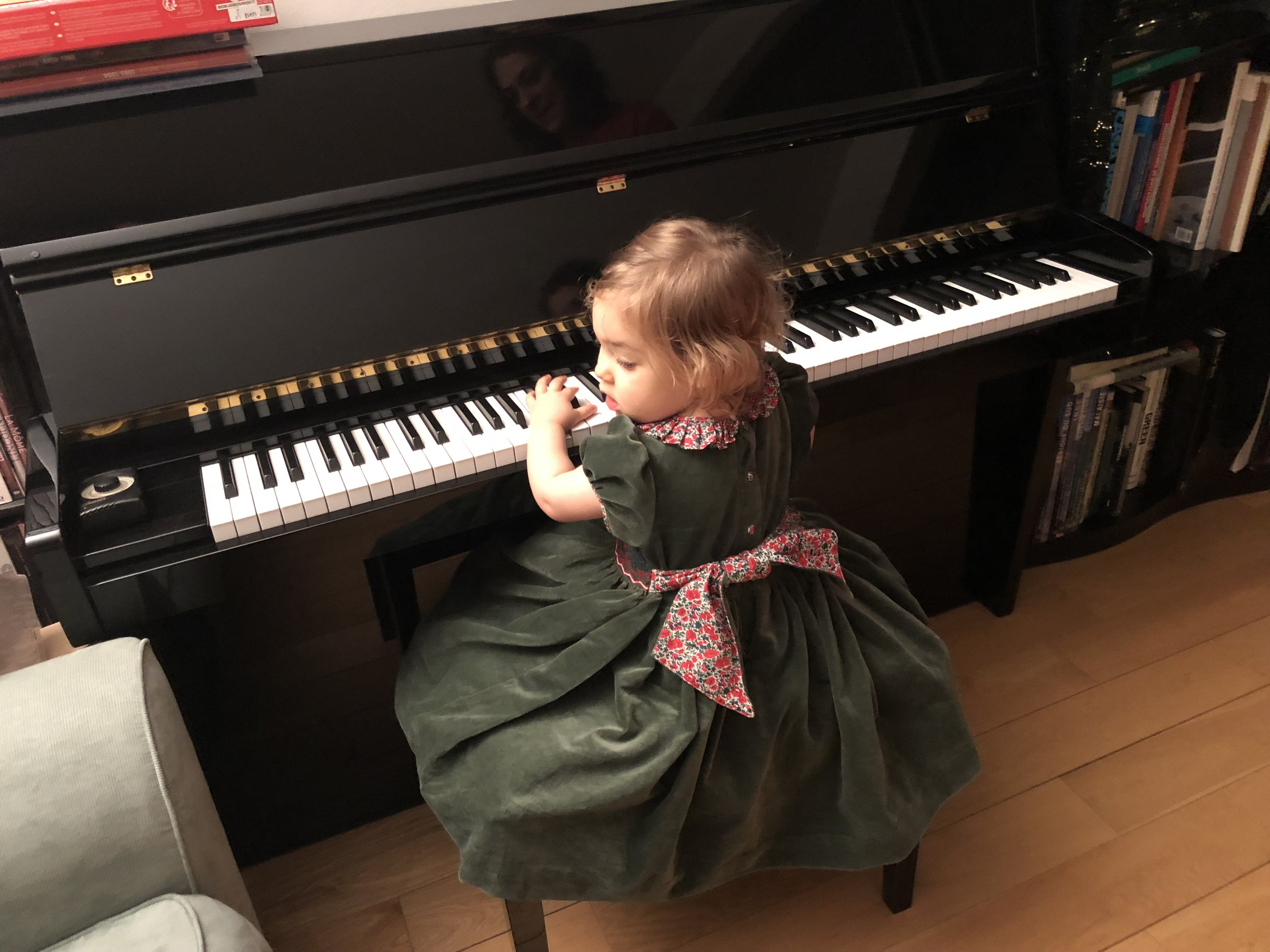 Beautiful Chiara playing the piano at Christmas in our fir green Liberty collar Amandine dress
