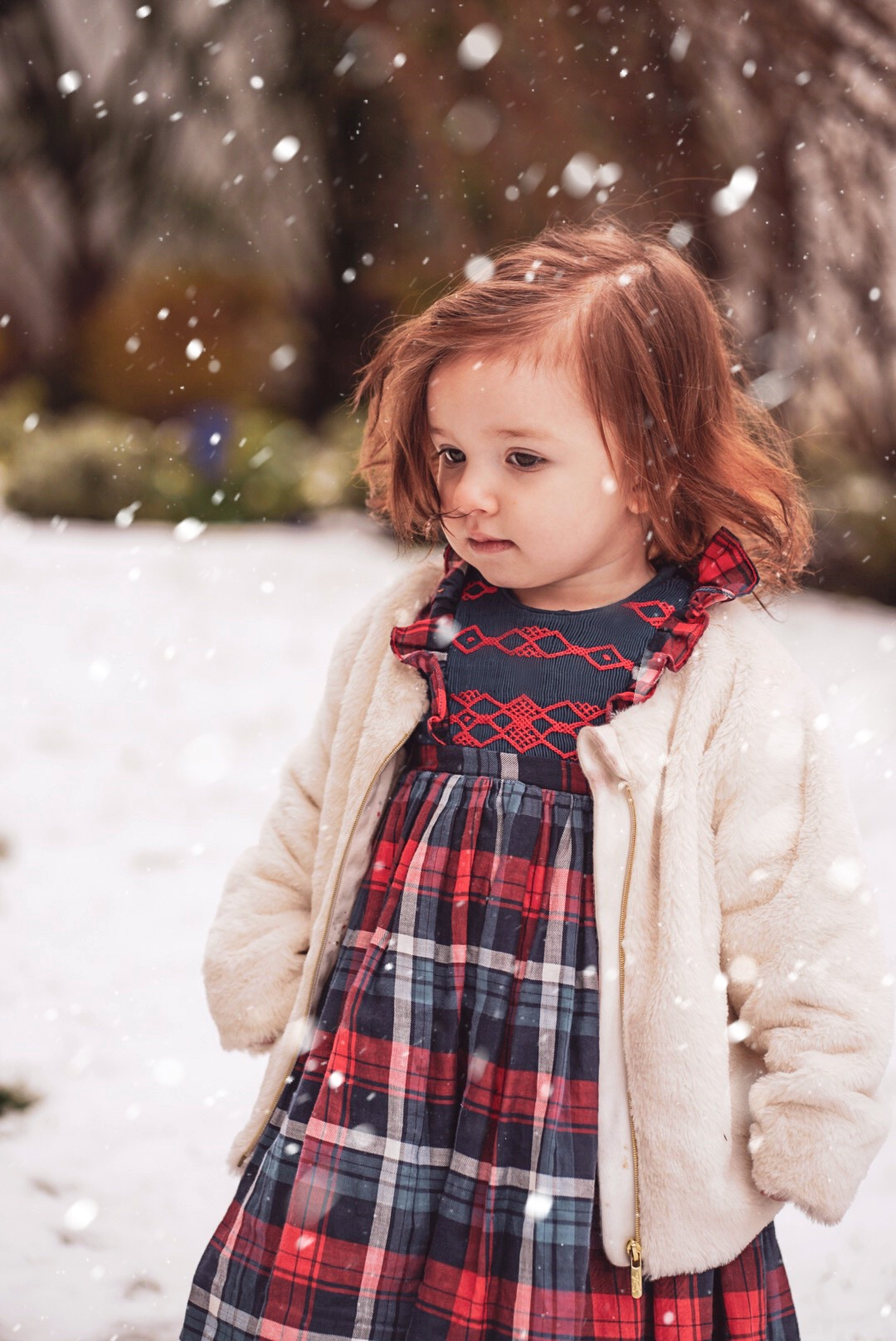 Amelie playing in the snow in her handmade Ninon smocked dress