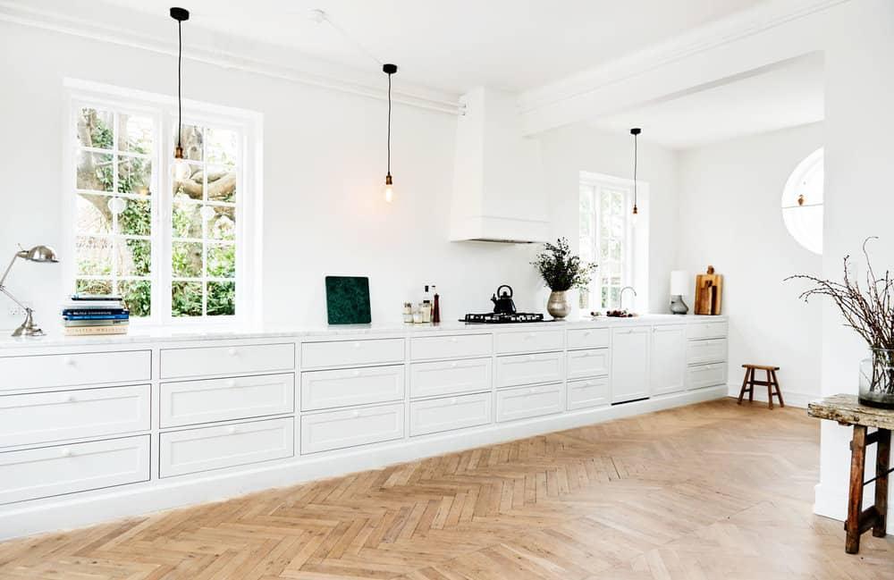 Stort hvidt køkken med skabe, skuffer, emhætte og opvaskemaskine