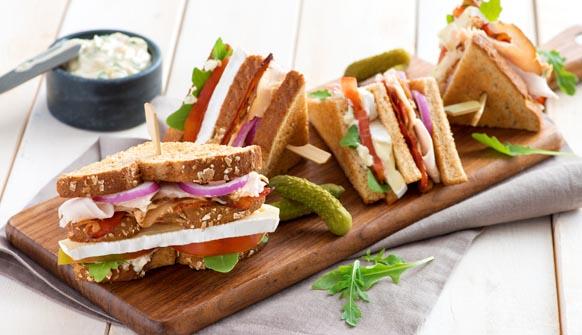 Club sandwich quarters on wood cutting board