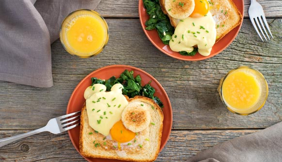Egg-in-a-hole toast with Wilted Hollandaise Sauce on table with glasses of orange juice