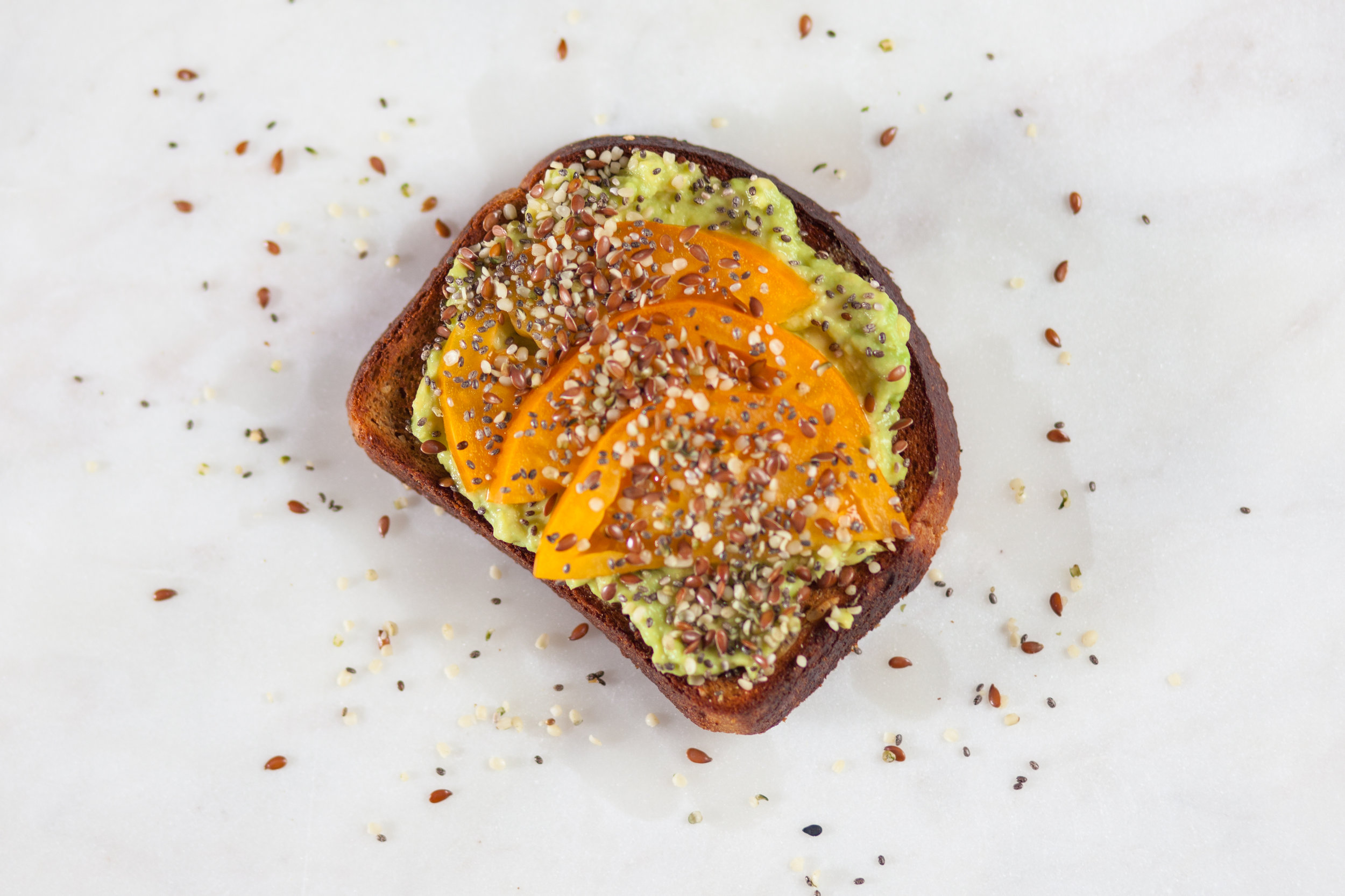 Toast topped with avocado paste and heirloom tomatoes