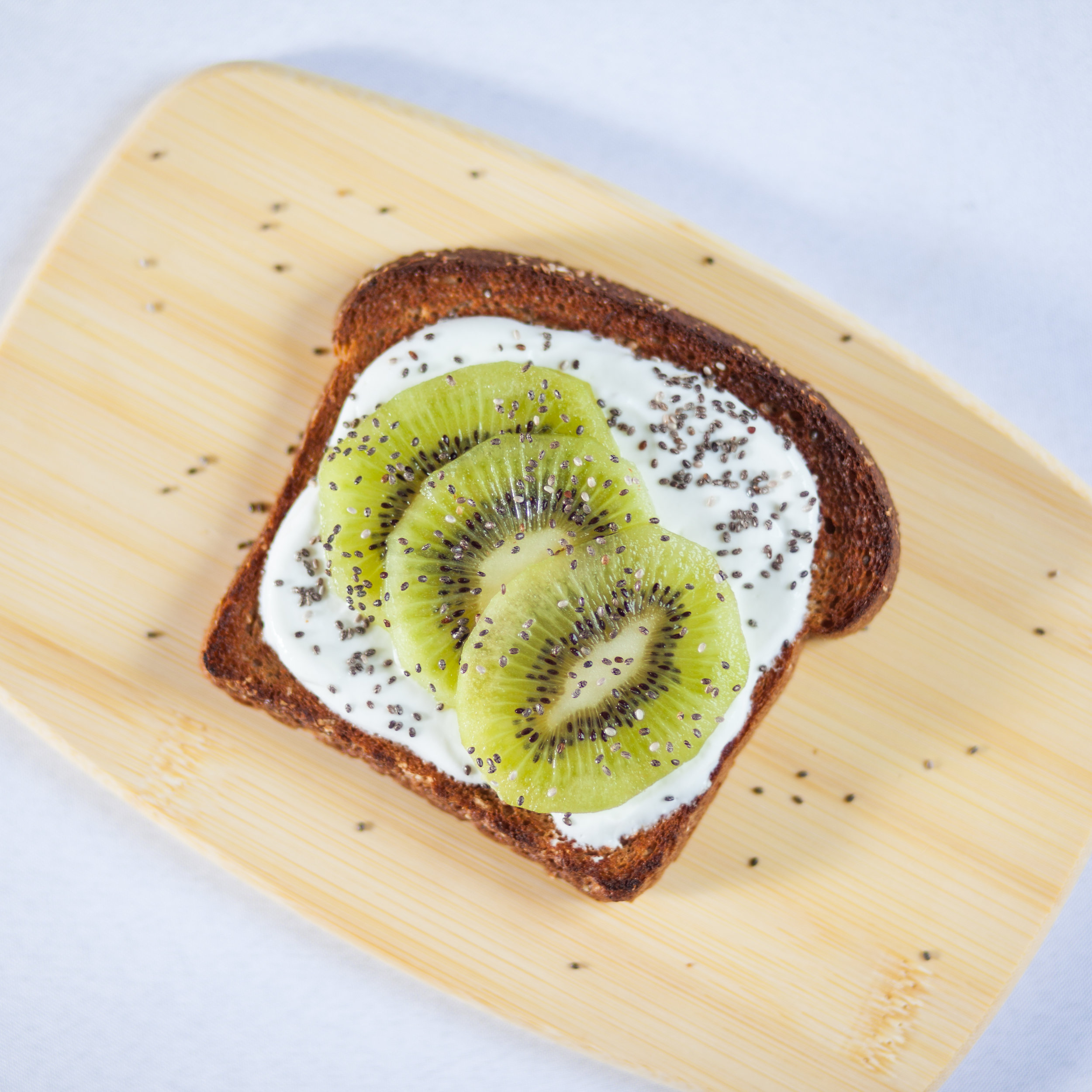Toast topped greek yogurt, kiwi slices, and chia seeds