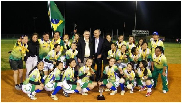 Don Porter, president of the International Softball Federation, left, and Mike Fennell, the president of the Jamaican National Olympic Committee, center, stands with the team from Brazil which won the Easton Foundation Youth World Cup at Plant City Stadium. The softball federation director of competition, Laurie Gouthro, standing second from the left, joined the celebration