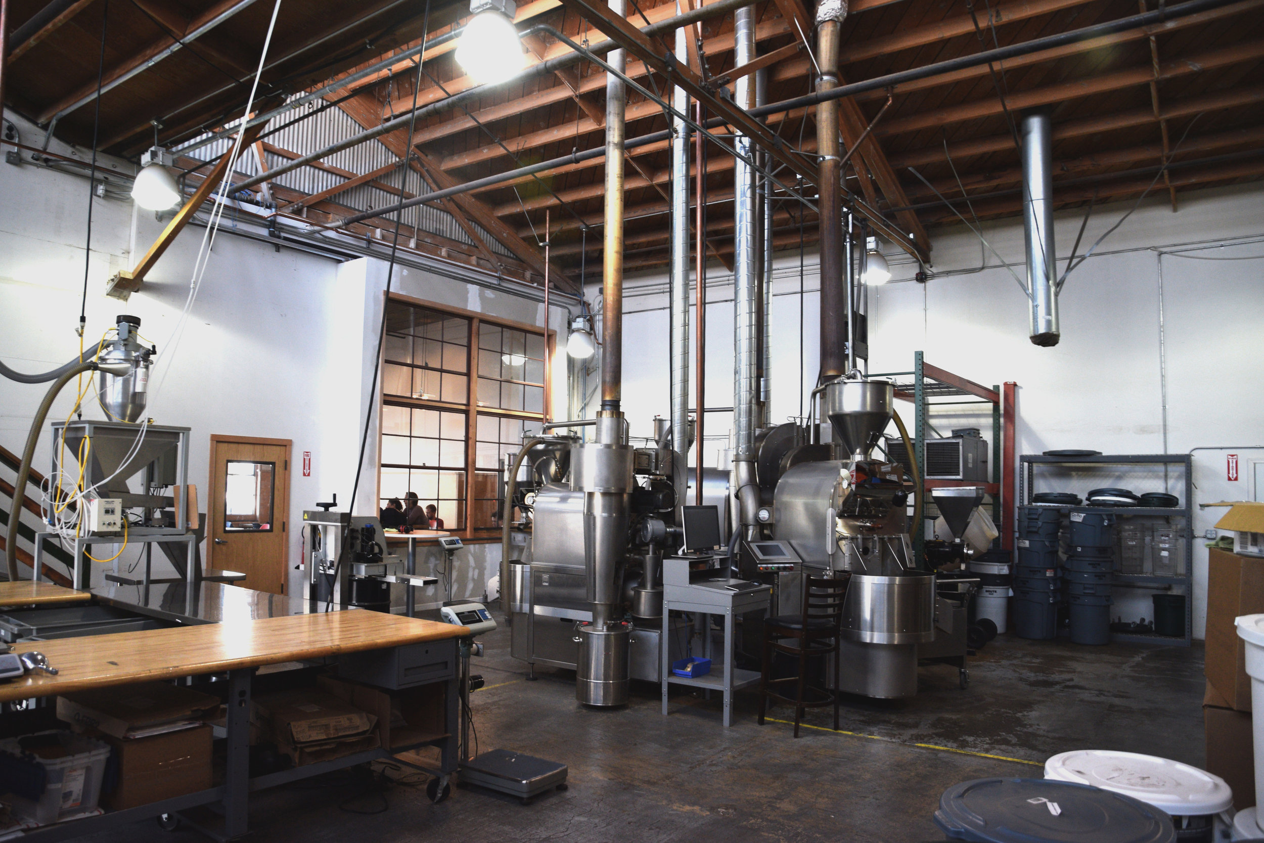 CoRo's collaborative coffee roastery with four state-of-the-art roasting machines & automatic packaging equipment. Window looks into our adjacent cafe, which serves coffees roasted onsite by our member brands.