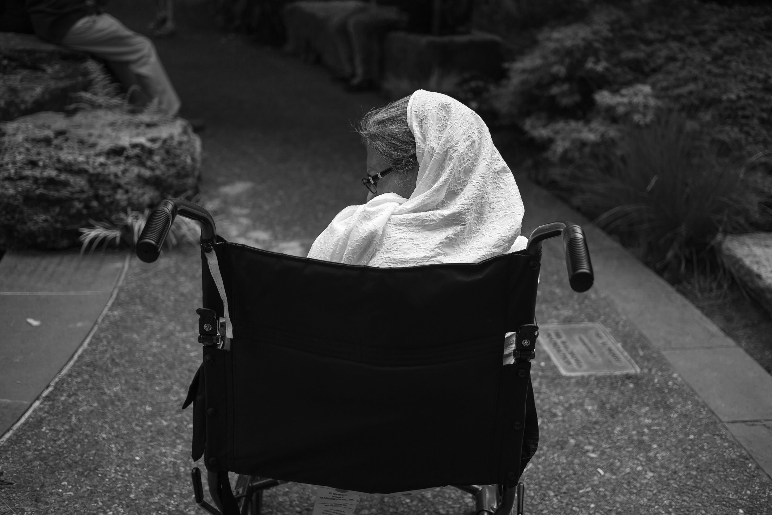 APRIL 28, 2019 | A WOMAN SITS ALONE ON HER WHEELCHAIR, WHILE HER FAMILY TAKES SELFIES AT THE DALLAS ARBORETUM.