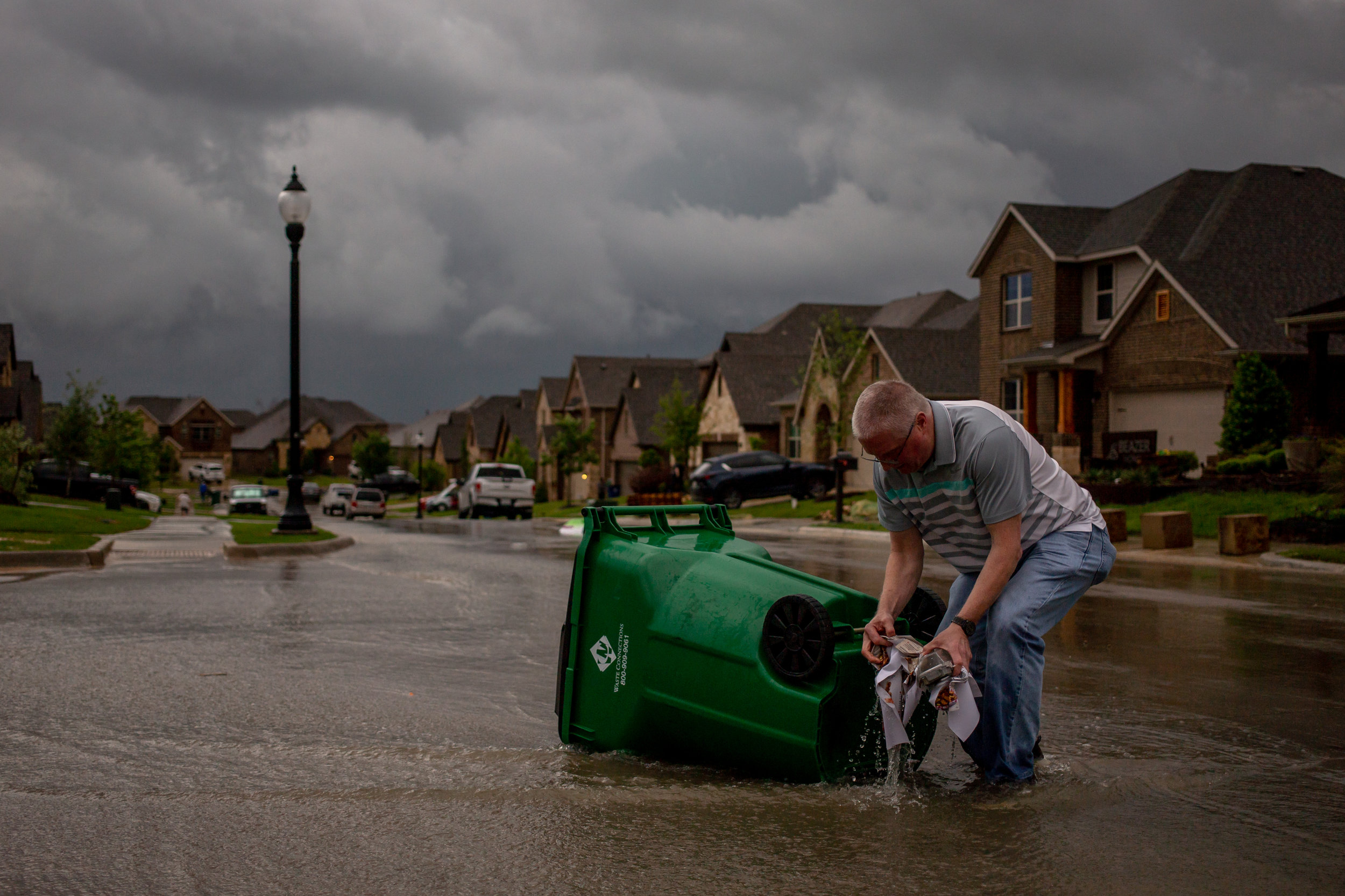 APRIL 30, 2019 | A CANYON FALLS RESIDENT RETRIEVES HIS TRASH CAN THAT PICKED UP AND BLEW AWAY DURING A TORNADO IN NORTHLAKE, TEXAS.