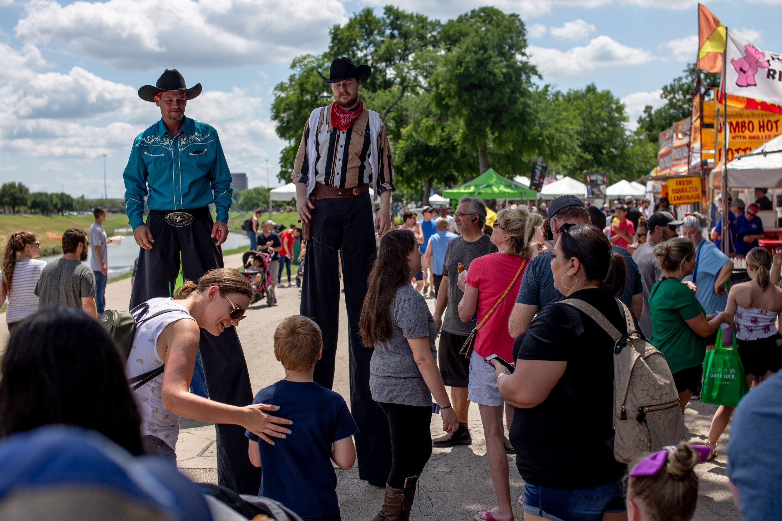 APRIL 05, 2019 | TWO COWBOYS ON STILTS WALK AROUND MAYFEST IN FORT WORTH, TEXAS.