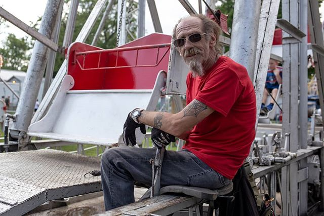 Terry, a gypsy ferris wheel operator, sits and poses for a picture as he pulls the lever for the popular Grange Fair ferris wheel. #grangefair #gypsyman #americandailylife #portrait