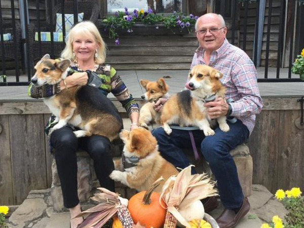 Nancy Jones and her husband Mike with their Corgis.