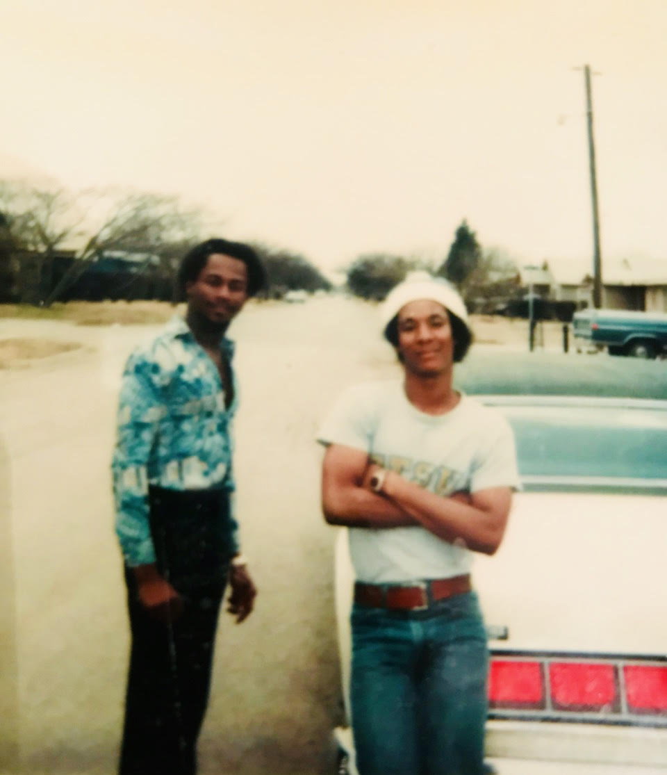 Carl as a young man (leaning on the car).