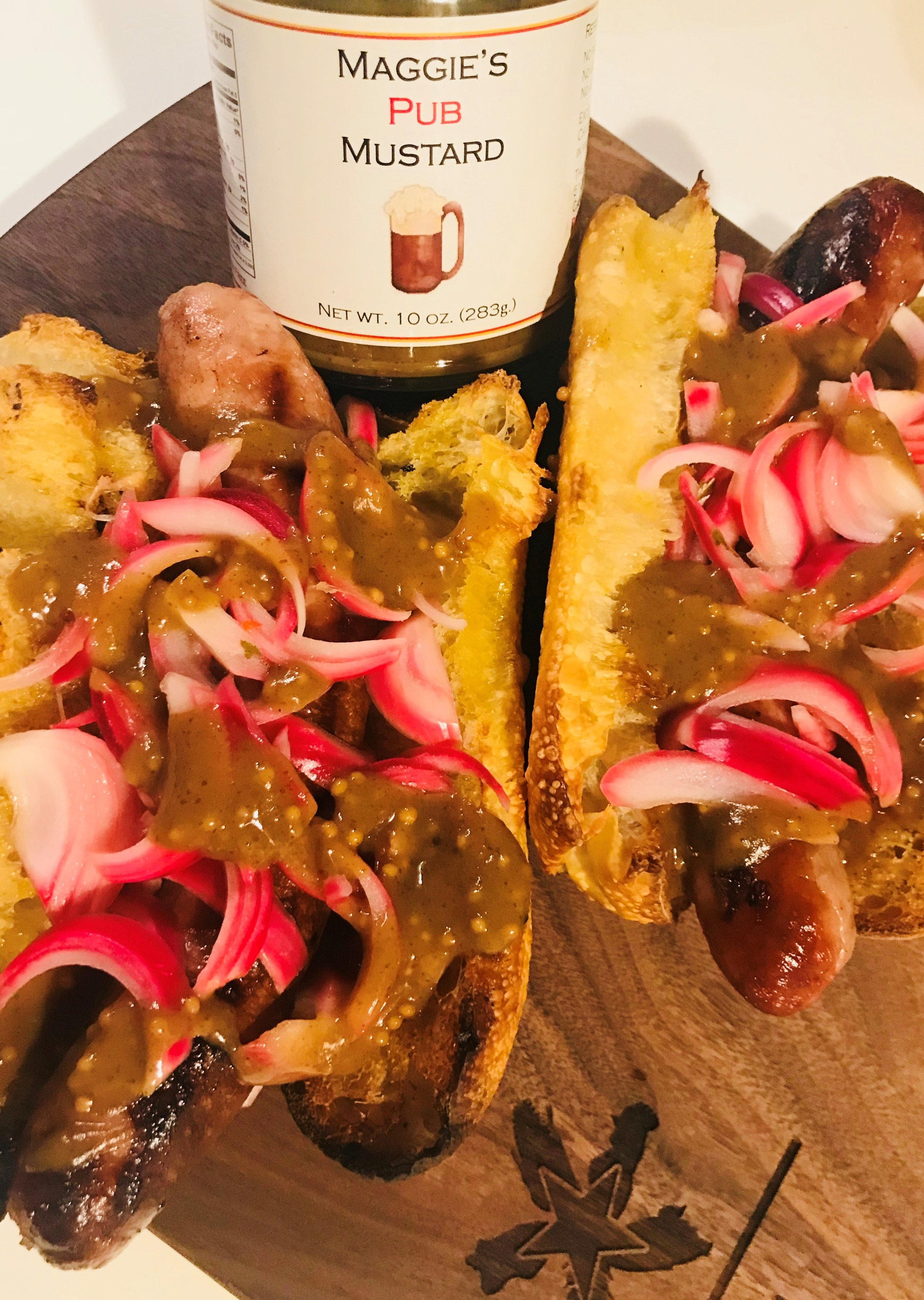 Apple Cider Brat with IPA pickled red onions on a fresh roll covered in our Pub Mustard!