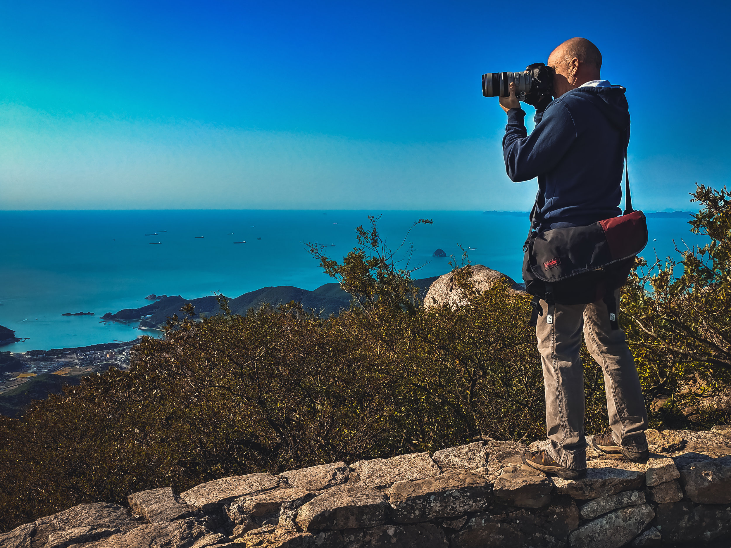 Tom photographing the South Korean seascape from atop Geumsan Mountain at a Buddhist Temple known as Boriam Hermitage. (Photo Credit - Kathryn Burns Oliver, 2018)