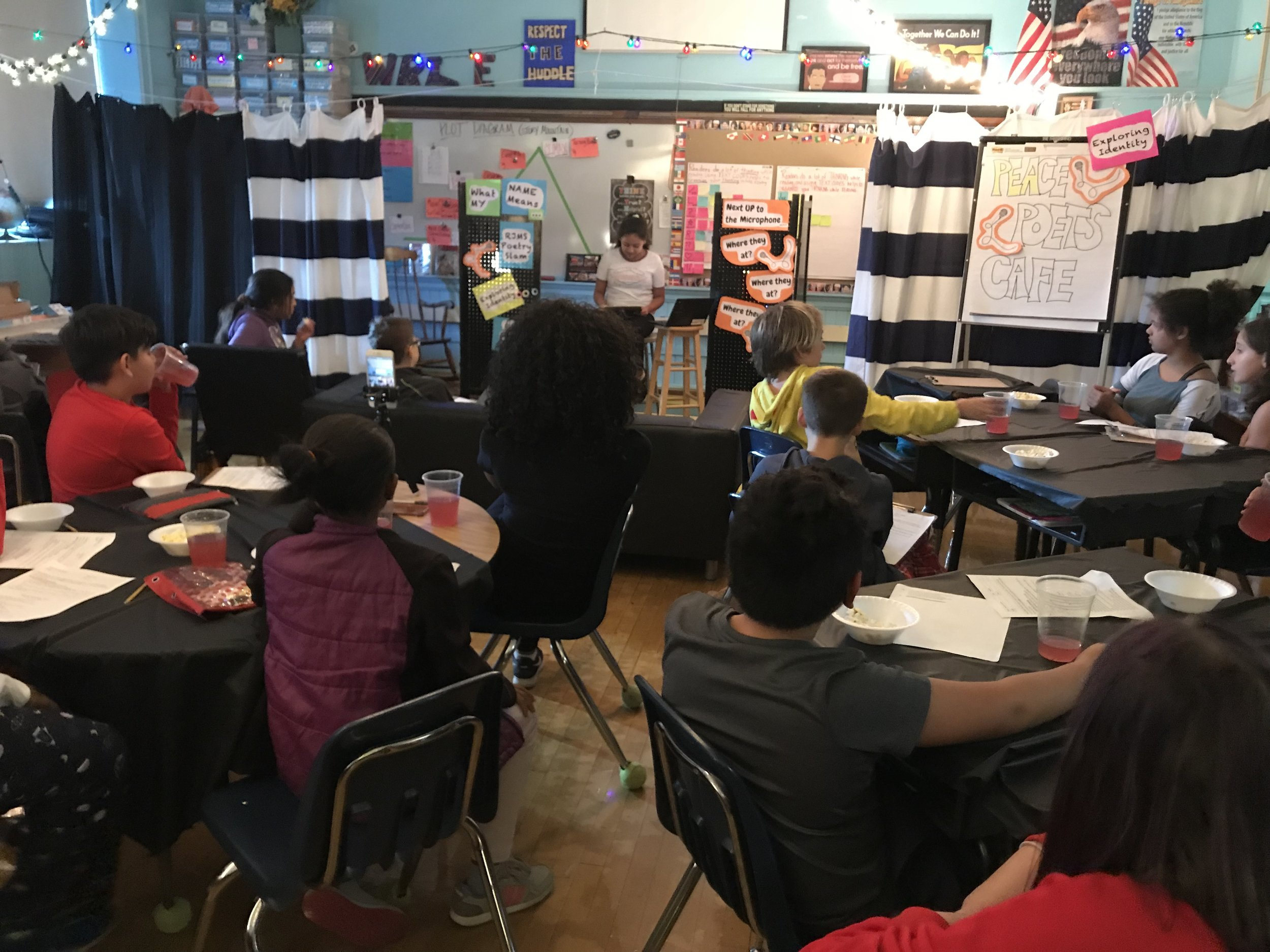 RJMS students participate in a classroom Poetry Slam, complete with beverages, snacks, and a coffee-shop ambiance.
