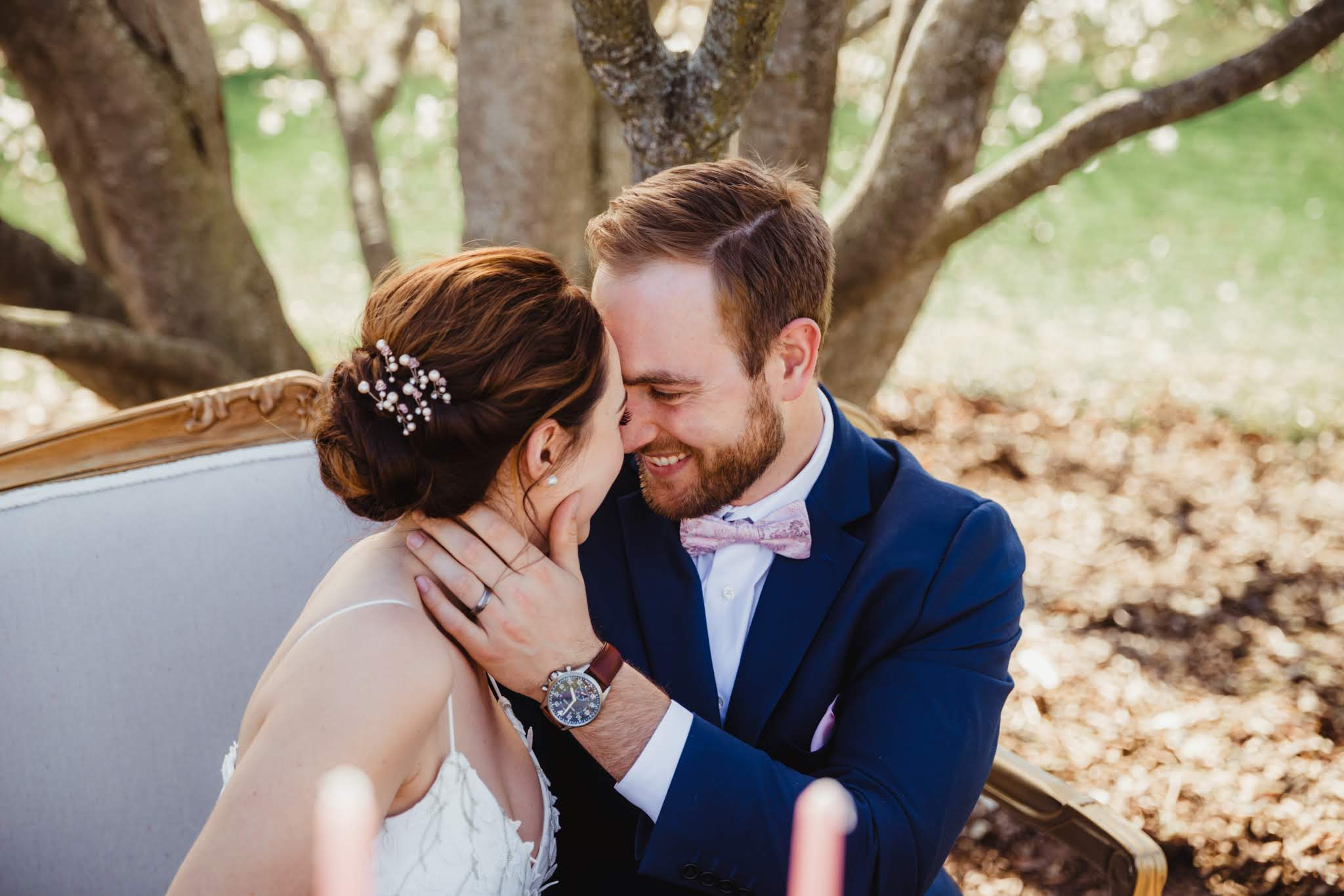 Bride and Groom Snuggling at the Sweetheart Table - Spring Wedding at the UW Madison Arboretum in Madison Wisconsin - Phoenix & Rose Photography