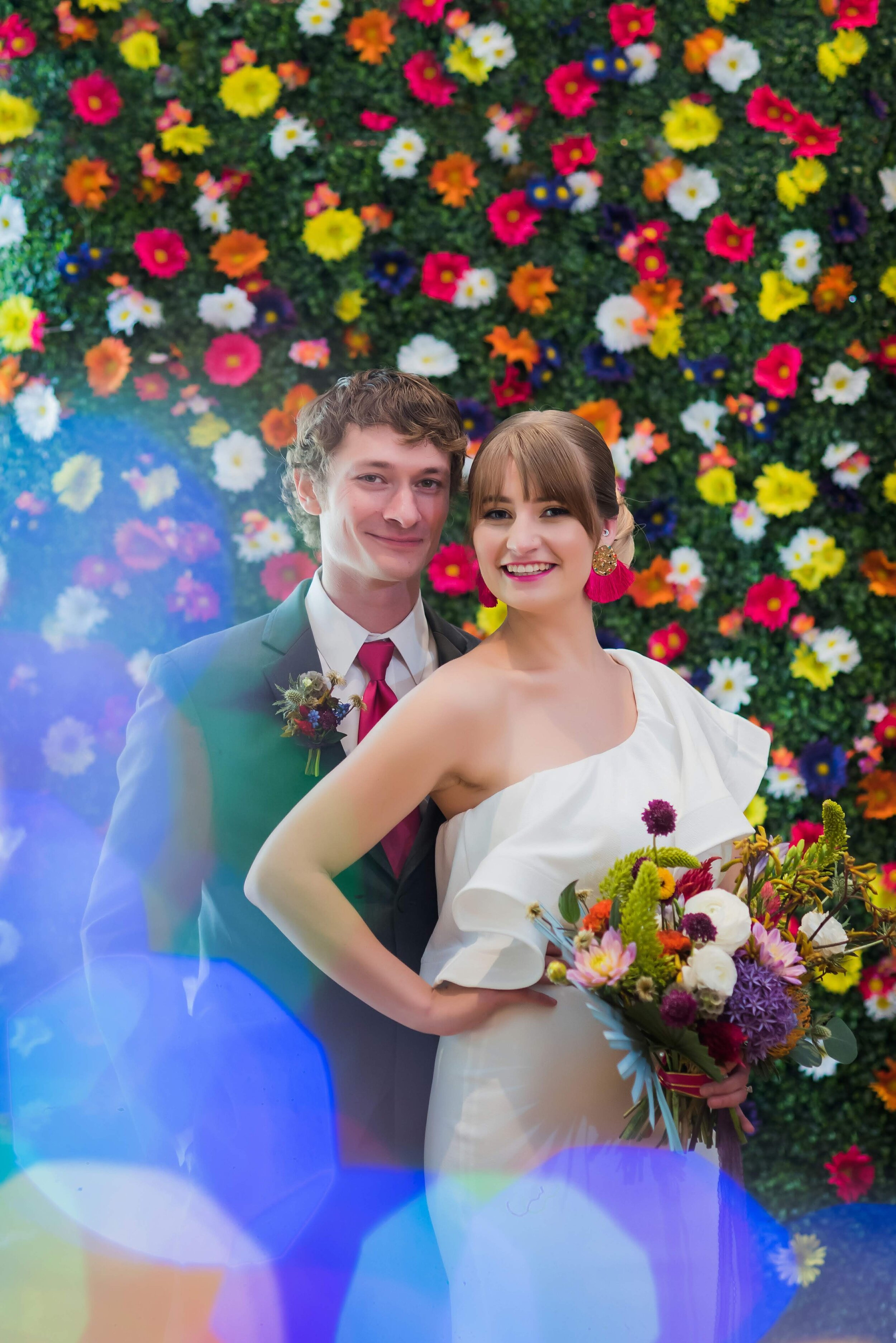 Bride and groom with a floral photo backdrop at their wedding at Charles Allis Art Museum in Milwaukee, Wisconsin- Photo by Reminisce Studio.jpg