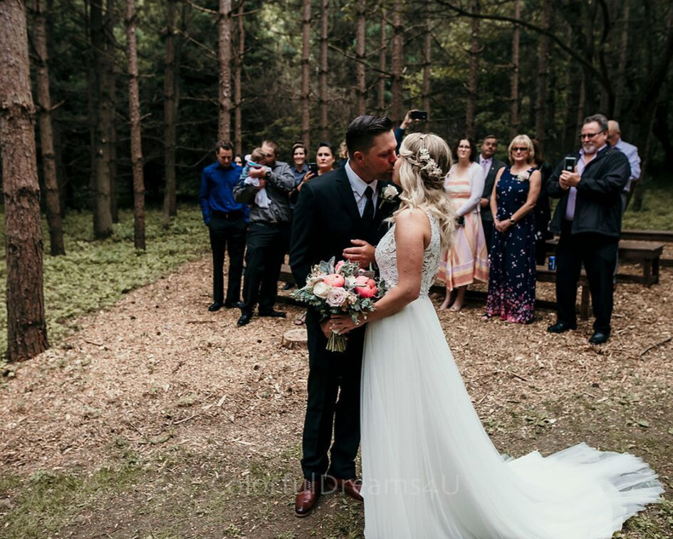 Bride and groom kissing right away at their ceremony - June backyard intimate summer wedding in Hubertus Wisconsin - Planned by Natural Elegance LLC - Photo by Colorful Dreams 4U.png
