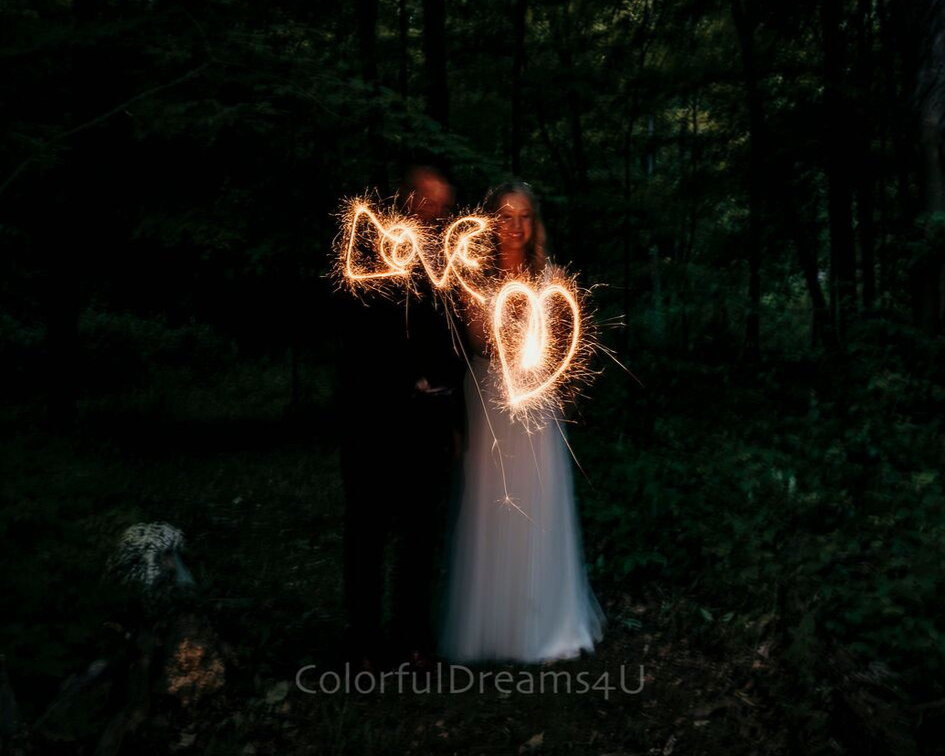 Bride and groom writing love with sparklers at their June backyard intimate summer wedding in Hubertus Wisconsin - Planned by Natural Elegance LLC - Photo by Colorful Dreams 4U.png
