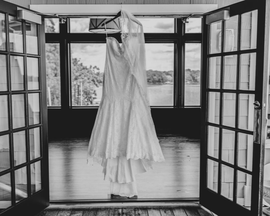 Brides wedding dress hanging from a door frame at the Oconomowoc Lake Club - Wedding planned by Natural Elegance LLC and Photo by Faith Photography.png