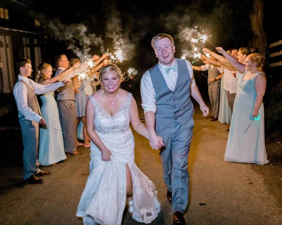 bride and groom running through their sparkler send off from a lake club wedding at the Oconomowoc Lake Club in Wisconsin - Wedding planned by Natural Elegance LLC and Photo by Faith Photography.png