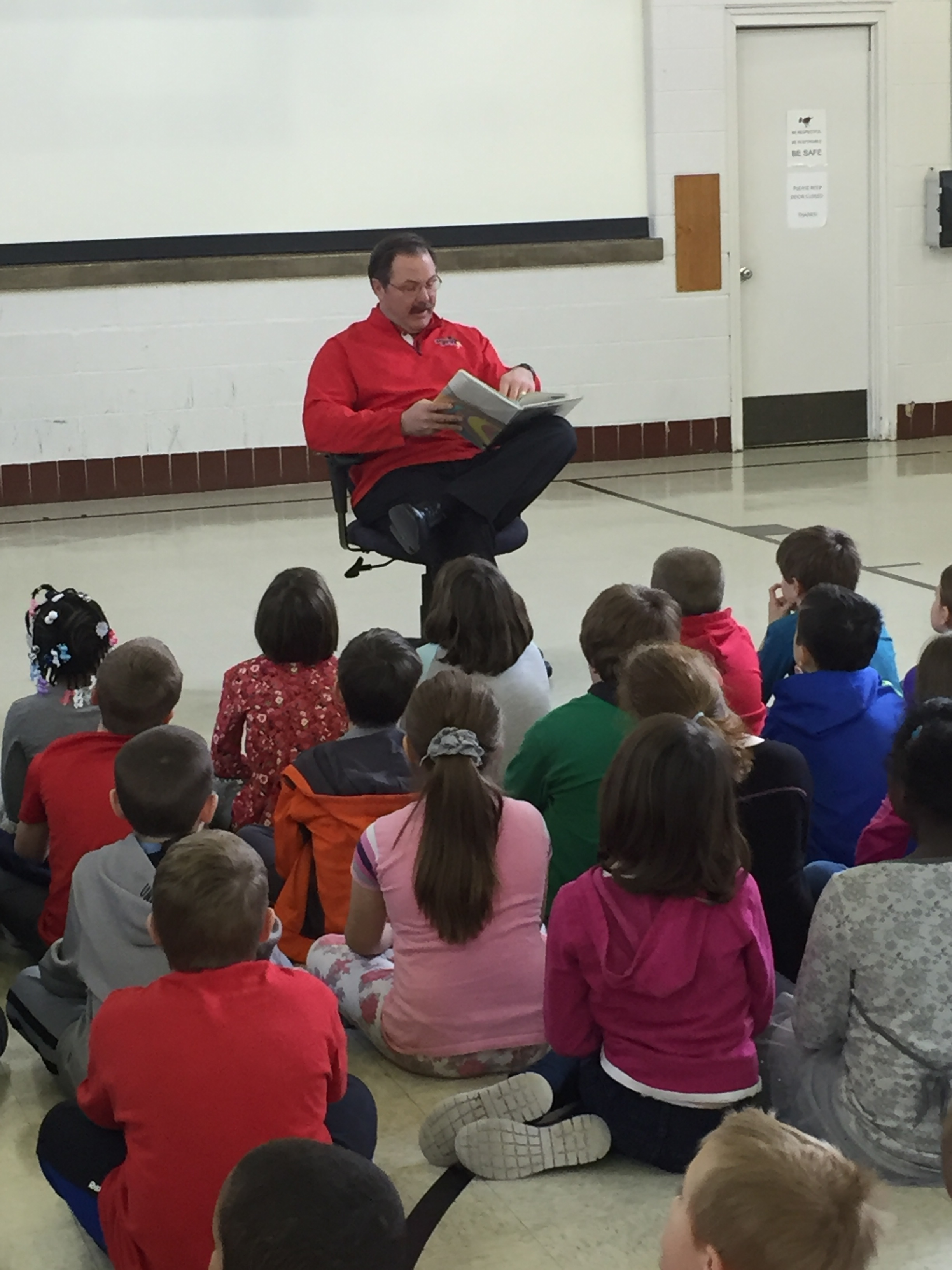 "ISU Football Coach Brock Spack reading to kids at Fairview Elementary School as a part of United Way of McLean County's annual ""Read Across McLean County Event"