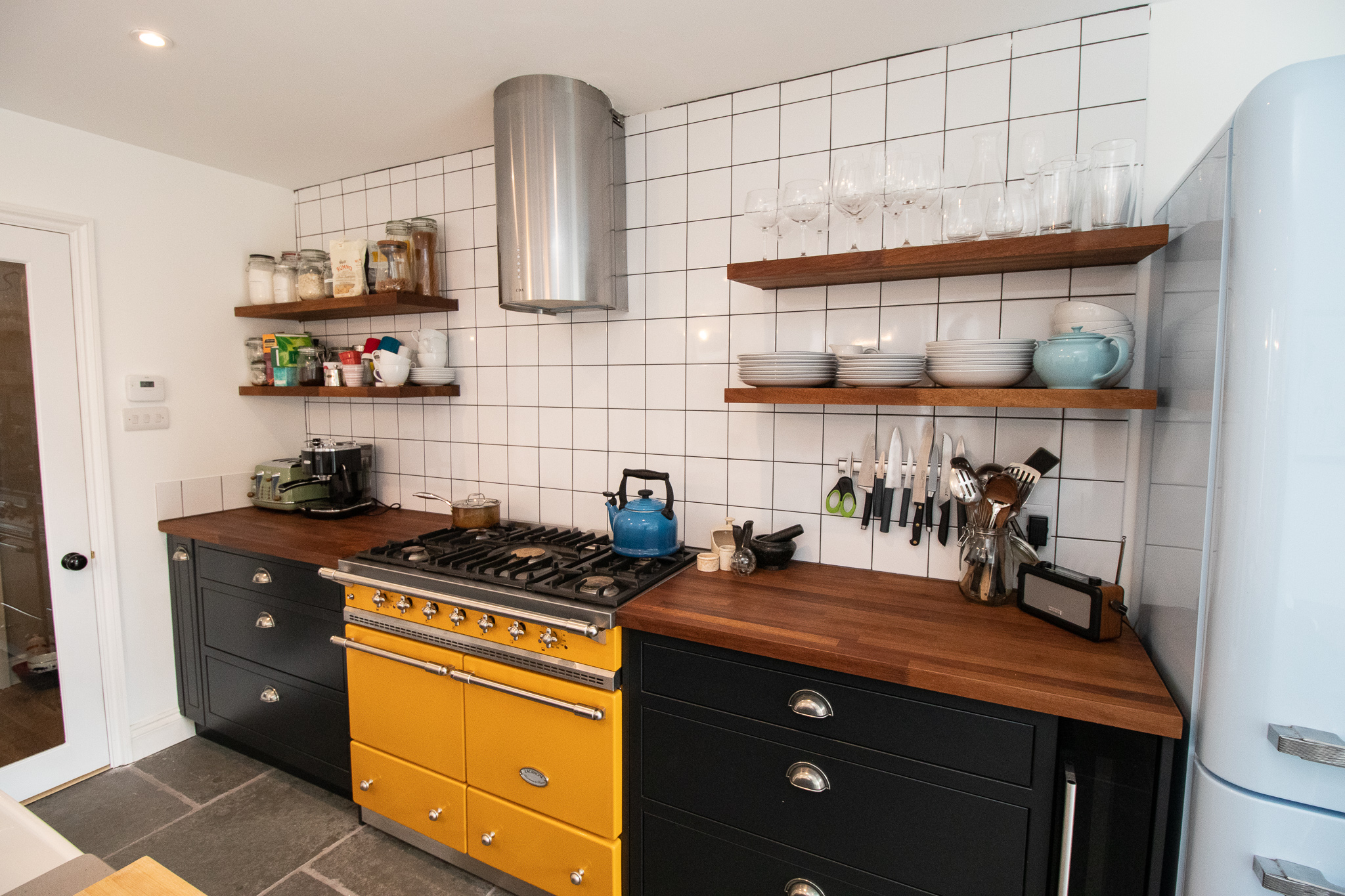 SMEG COOKER, SMEG FRIDGE, BLACK KITCHEN, MULTI COLOURED KITCHEN, OPEN SHELVES, WOODEN SHELVES, WOODEN COUNTERTOP.jpg