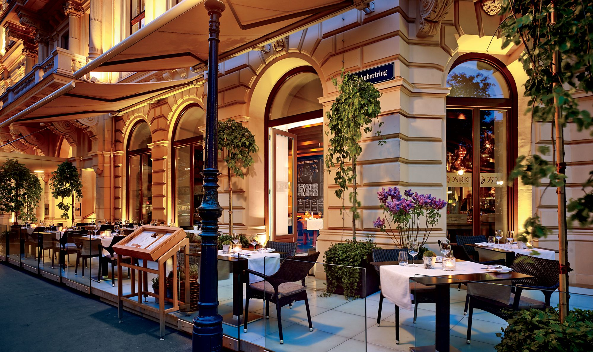 Patio seating wraps around the corner of the building and features potted plants and tables at the Ritz-Carlton in Vienna, Austria.