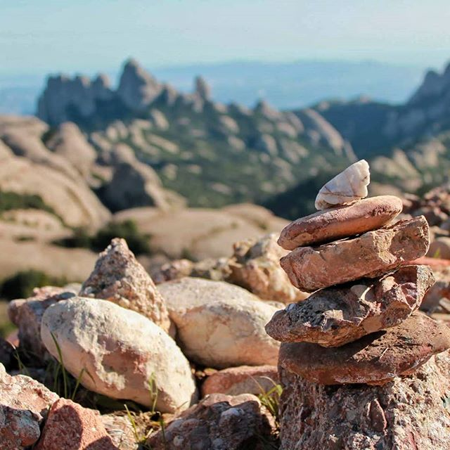"""Who'd have thought such rock piles could be a point of contention? Hm? Anyone? 🤔🤔 •• Not me, that's for sure, though I always did wonder why people built them. Seems about as frustrating an endeavor as playing golf. 🏒🏒 •• So I did some research before posting this pretty pile of rocks in front of the Montserrat mountain backdrop and it turns out - rock piles are a pretty controversial issue. 😶😶 •• The original rock piles, called Cairns - because they were Scottish, I guess, or maybe Celtic, I didn't research them THAT well - were set up as trail or grave markers. They were - are - solidly built, usually a lot bigger than this one, and can survive a thunderstorm without collapsing. ⛰⛰ •• On the other side of the issue are these smaller, shorter-lived piles. Some people build them for meditative purposes. Others do it just for fun, I guess. 🤸♀️🤸♀️ •• Sounds harmless, right? But not everyone agrees. Just google """"rock pile meaning"""" and you'll find several posts begging people to stop stacking rocks willy-nilly. One of the reasons is that moving rocks increases erosion by exposing the soil underneath, allowing it to wash away and thin soil cover for native plants. Every time a rock is disturbed, an animal loses a potential home, since many insects and mammals burrow under rocks for protection and reproduction. But regardless, nobody seems to know WHY people have started doing this. 🤷♀️🤷♀️ •• So here's my question: have you ever piled rocks into a stack like this? If so, why? No judgement, I'm really just curious. ❔❓🤔🙏 • • • • • #curiositykilledthecat #rockpile #mindfulnomad #bemindful #mindfulliving #mindfuleating #mindfullife #mindfulmoments #meditations #meditatedaily #meditating #meditative #meditationquotes #meditationpractice #meditationspace #nomadsoul #digitalnomads #digitalnomadgirls #digitalnomadlife #digitalnomadlifestyle #digitalnomadfamily #digitalnomade #digitalnomadspirit #digitalnomaddiary #digitalnomadism #digitalnomadinsider #girlslovetotravel #globalwan"""