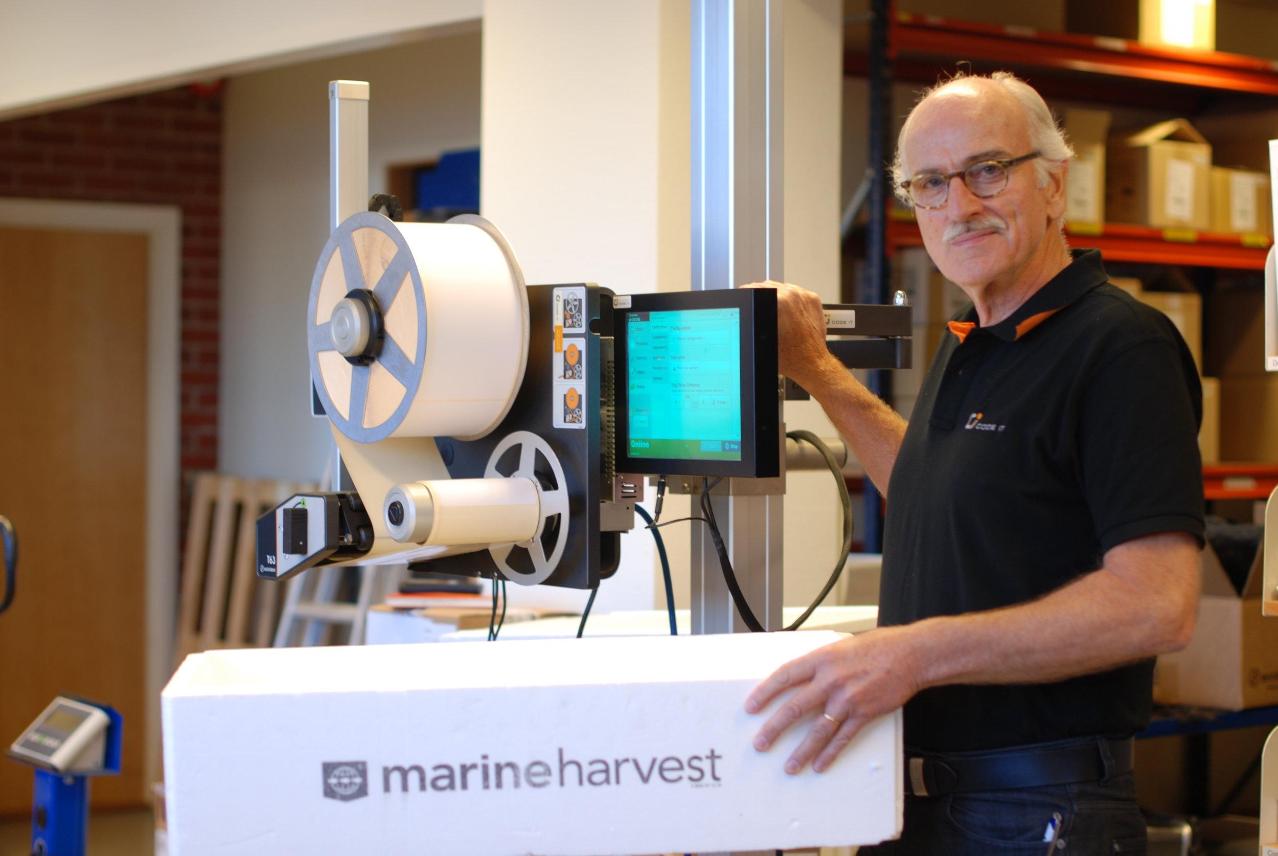 Bjørnar Torsnes, daglig leder i CodeIT, foran etiketteringsmaskinen med egenutviklet programvare som gjør sporing enklere. (Foto: Marit Letnes)