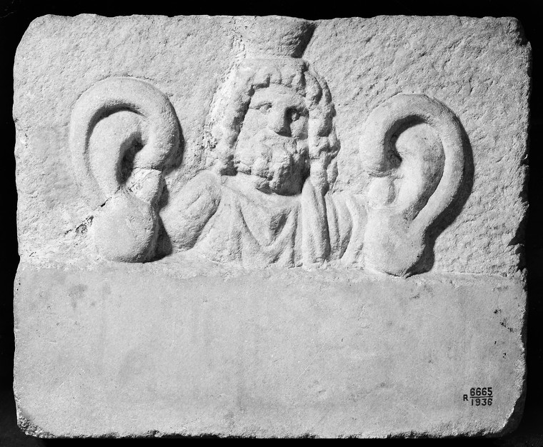 Marble votive plaque with relief bust, possibly Serapis, flanked by ears, Roman, from Italy, 100 to 300 CE. Image Credit: Wellcome Collection.